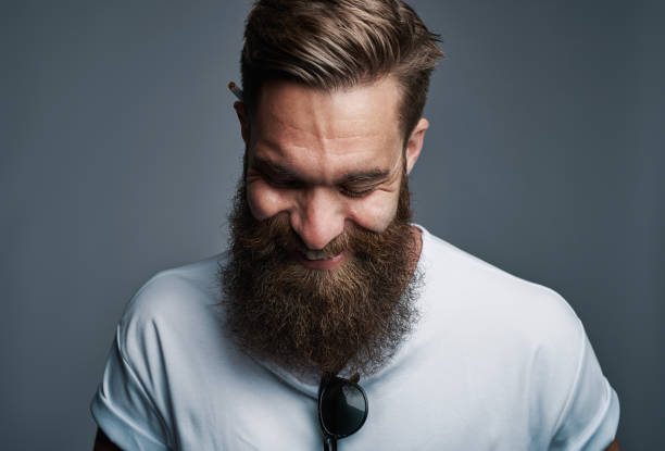 Giggling young man with large fuzzy beard stock photo