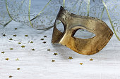 Gilded carnival mask, ribbon and gold stars on a light background. Selective focus.