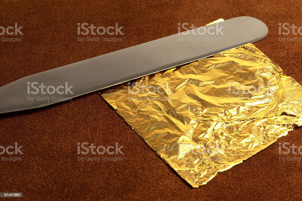 gilding theme with gold leaf and knife stock photo