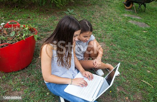 Gils using laptop in the garden