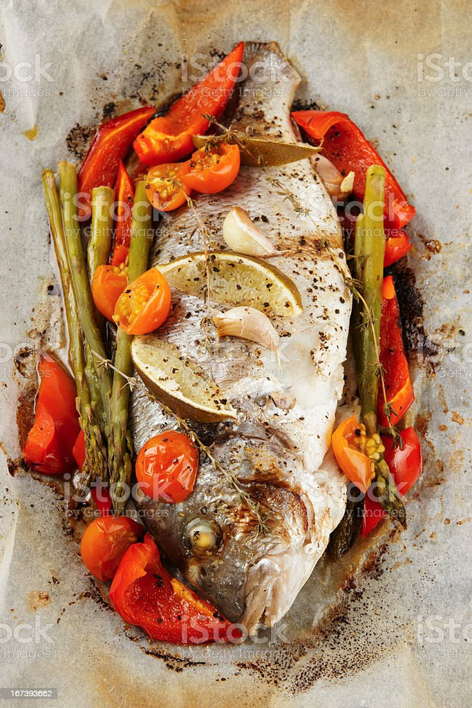 Gilt-head bream roasted with vegetables in paper royalty-free stock photo