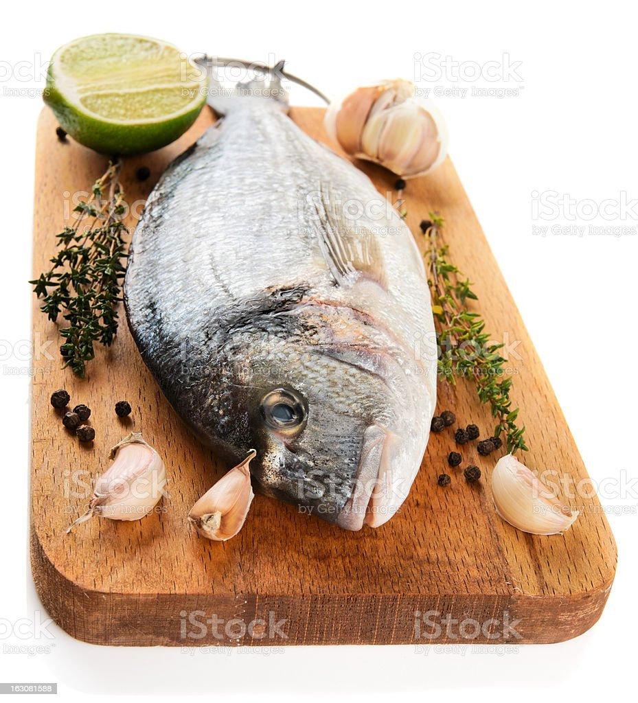 Gilt-head bream with herbs and spices isolated on white royalty-free stock photo