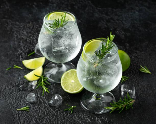 gin en tonic alcohol drinken met limoen, rozemarijn en ijs op rustieke zwarte tafel - gin tonic stockfoto's en -beelden