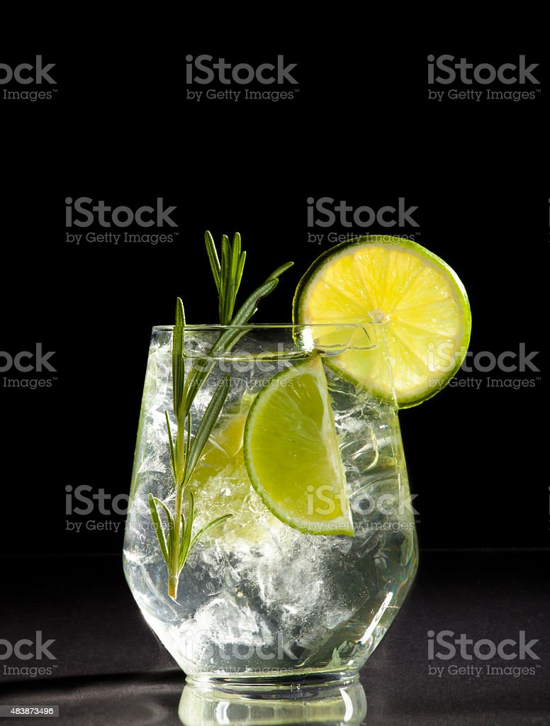 Gin and tonic cocktail with lime over black background. stock photo