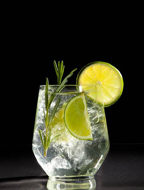cocktail avec Gin et tonique au citron vert sur fond noir. - Photo