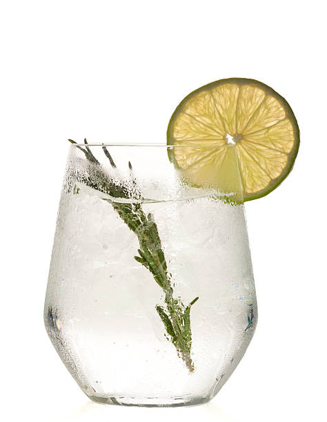 gin and tonic cocktail with lime over white background. - gin tonic stockfoto's en -beelden