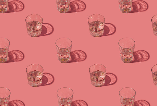 Gin and tonic crystal glasses garnished with rose buds and red peppercorns on a pastel pink background. Creative summer drink pattern.
