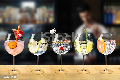 Gin and tonic mixed cocktail drinks various selection garnish bartender bar background fashion trendy