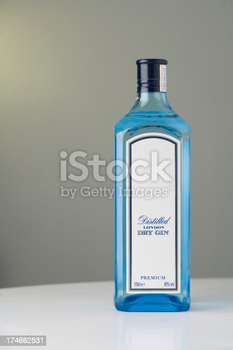 This is a product shot of a bottle of Gin. The glass is bright blue and full of liquid. The text has mostly been removed so your own can be added.