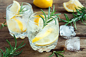 Alcoholic drink (gin tonic cocktail) with lemon, rosemary and ice on rustic wooden table, copy space