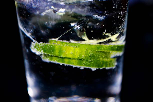 gin tonic: macro close-up van groene komkommer schijfjes met sprankelende bubbels en ijsblokjes in cocktail glas. zwarte achtergrond. - gin tonic stockfoto's en -beelden