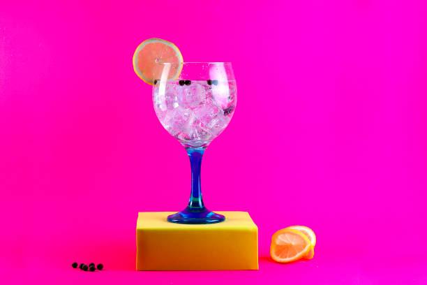 gin tonic auf blauem glas auf gelben sockel - zimt gurken stock-fotos und bilder