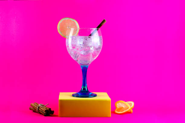 gin tonic auf blauem glas mit zitronenscheibe und zimtstange auf gelben sockel - zimt gurken stock-fotos und bilder