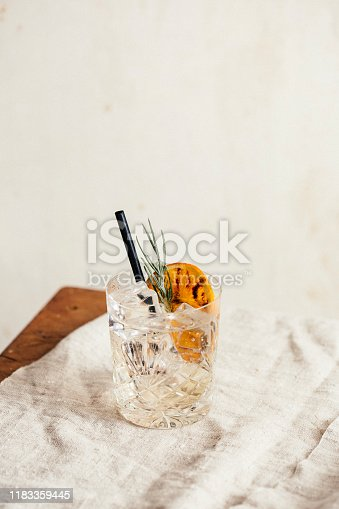 Gin tonic garnished with charred orange and lavender, on a rustic table