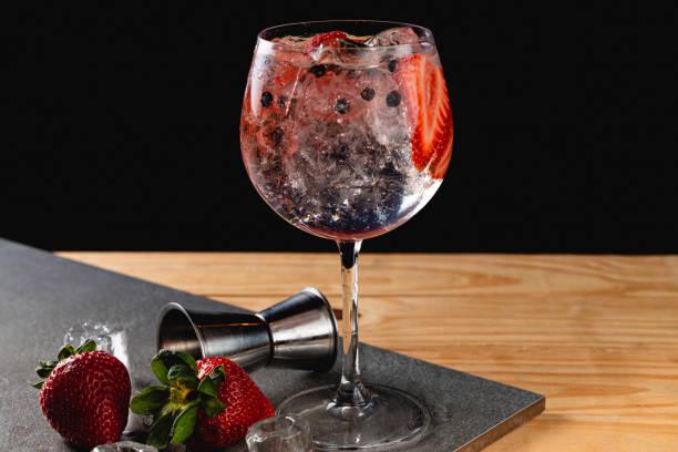 gin tonic aardbei met juniper stenen achtergrond in grijze kleur - gin tonic stockfoto's en -beelden