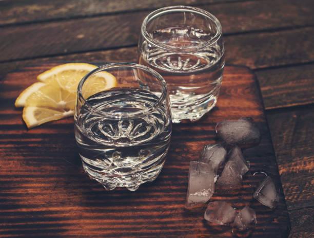 Gin Tonic, Wodka oder Rum mit Eis und Zitrone auf Holztisch. Retro-Stil Hintergrund. – Foto