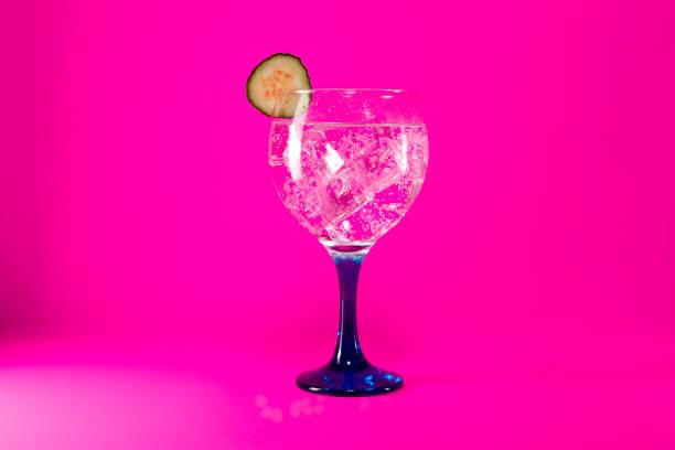 gin tonic mit gurke slice auf rosa - zimt gurken stock-fotos und bilder