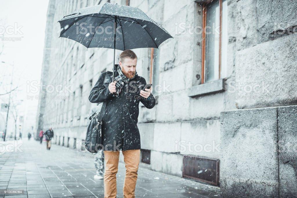 Ginger businessman walking in the snow, talking on mobile phone. Belgrade, Serbia, Europe stock photo