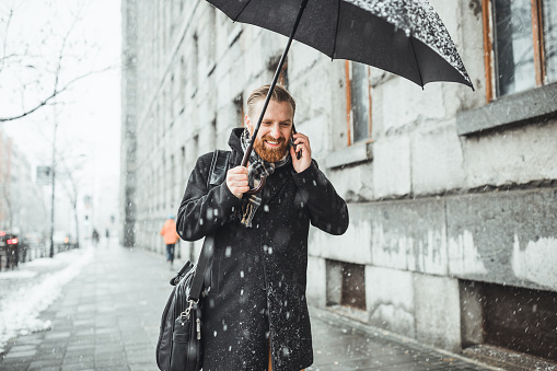 Ginger businessman walking in the snow, under the umbrella, using smart phone.