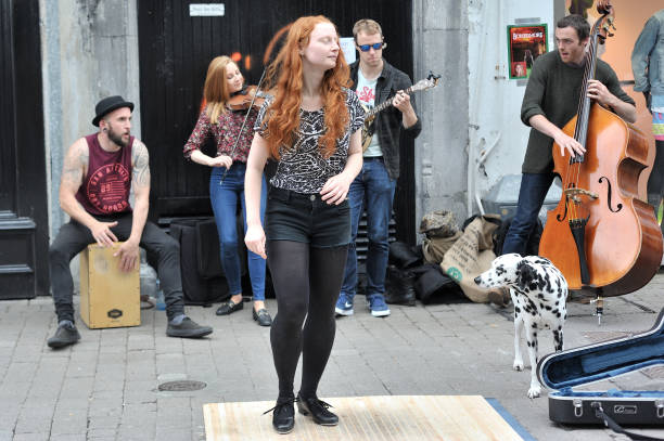 Ginger Hair Girl step dancing in the street with a group of Irish musicians stock photo