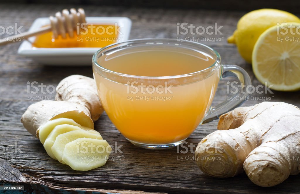 Ginger homemade tea infusion on wooden board with lemon stock photo