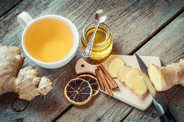 ginger, jar of honey, tea cup on kitchen table. - ginger stock photos and pictures