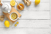 Ginger Lemon Tea with Honey. Warming immune boosting tea with lemon and ginger. Cup, teapot, ginger root on white wooden background, top view, copy space.