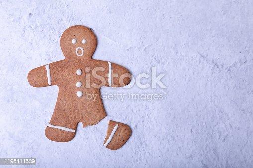 Имбирный человечек со сломанной ногой (без ноги) и с удивлённым лицом. Традиционное новогоднее и рождественское домашнее печенье. Выборочная фокусировка, крупные план. Место для текста.