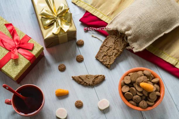 ginger nuts, jute zak en gouden geschenk voor nederlandse evenement sinterklaas - cadeau sinterklaas stockfoto's en -beelden