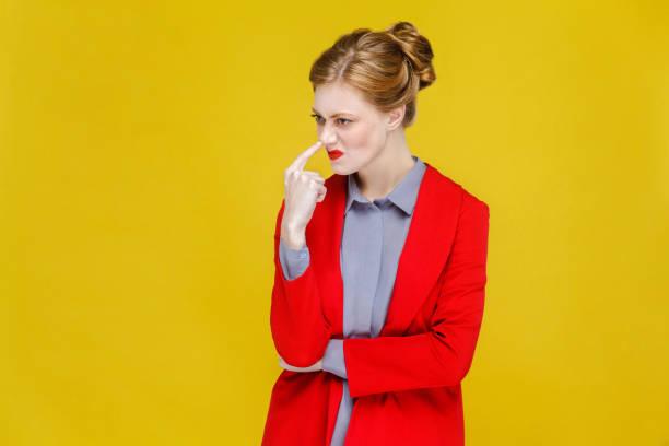 ingwer roter kopf geschäftsfrau im roten anzug zeigt lügner, bizarre zeichen. - pig ugly stock-fotos und bilder