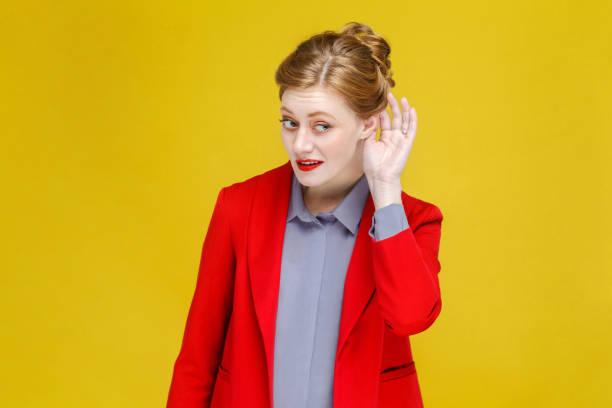 femme de tête rouge gingembre en costume rouge écoute secret. s - indiscret photos et images de collection