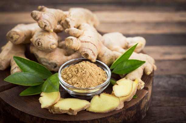 ginger root and ginger powder in the bowl - ginger stock photos and pictures