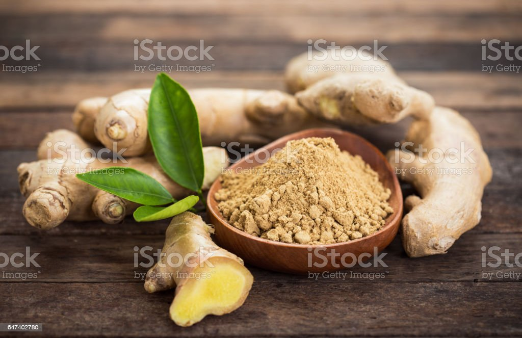 Ginger root and ginger powder in the bowl stock photo