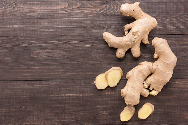 ginger root on the wooden background. top view - ginger stock photos and pictures