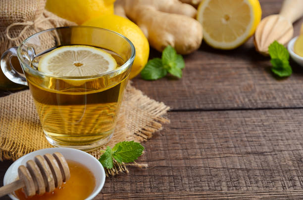 Ginger root tea with lemon and honey on wooden background. stock photo