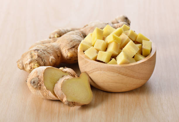 ginger sliced in wood bowl - ginger stock photos and pictures