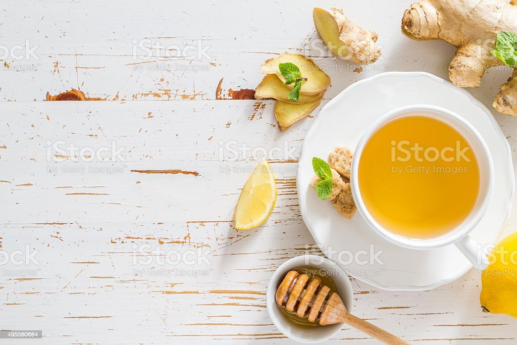 Ginger tea and ingredients on white wood background stock photo