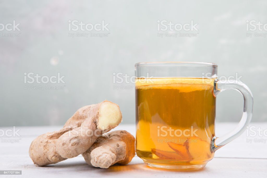 Ginger tea in a glass cup on wooden background stock photo