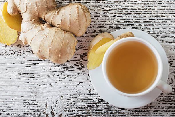 ginger tea in a white cup on wooden background - ginger stock photos and pictures
