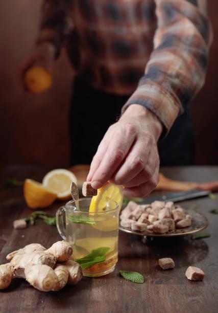 ingwertee mit braunem zucker, zitrone und minze auf alten holztisch. - ingwerwasser zubereiten stock-fotos und bilder