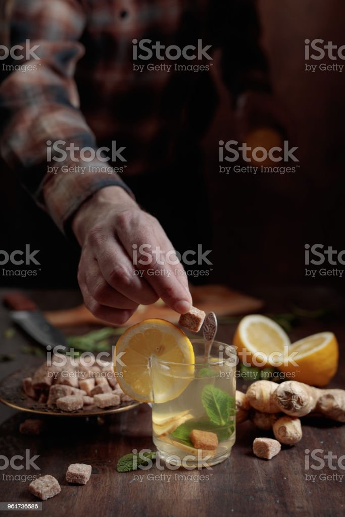 Ginger tea with brown sugar , lemon and mint on old wooden table . royalty-free stock photo