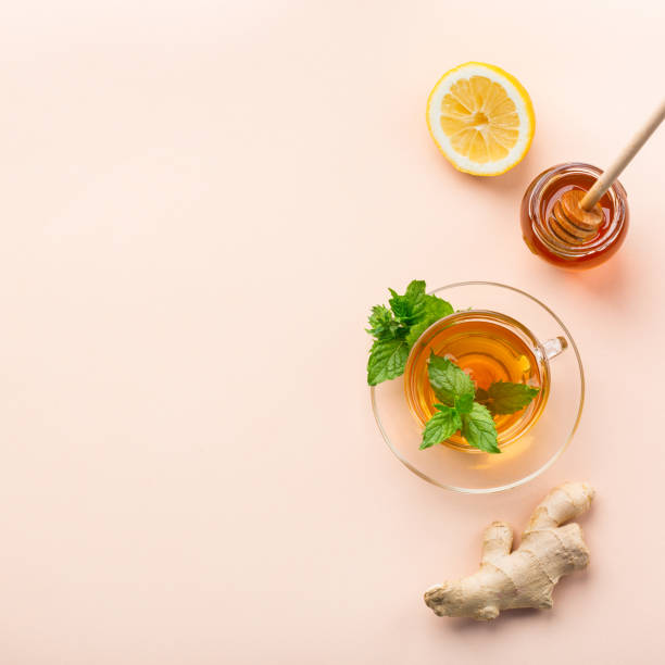 Ginger tea with mint, lemon and honey on coral table stock photo