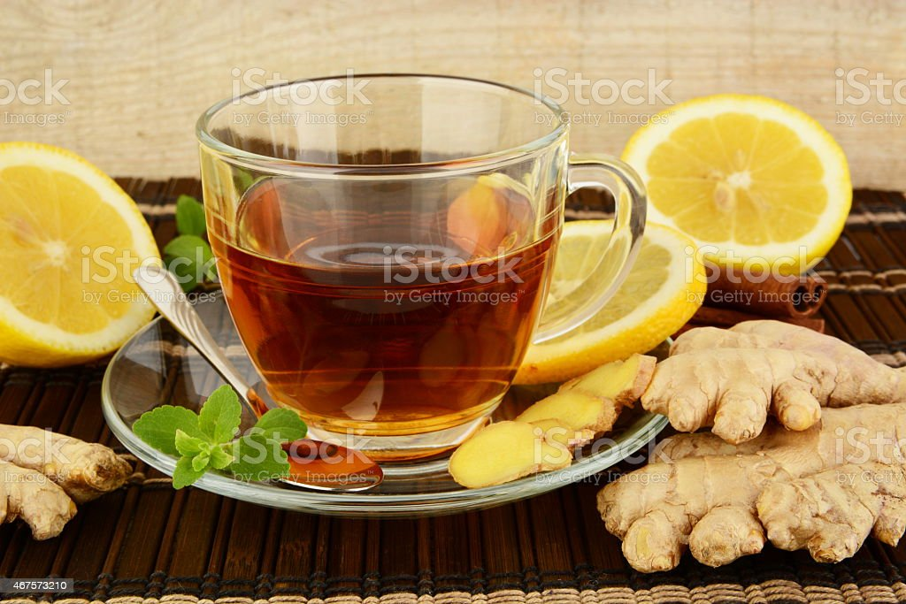 Ginger tea-ingwertee on brown mat with lemon stock photo