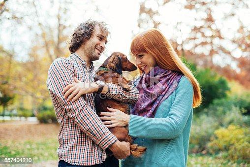 istock Ginger woman petting dachshund dog 857404210