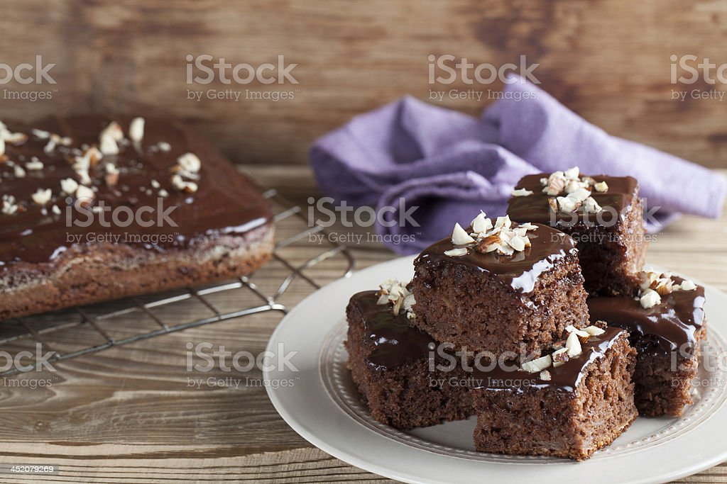 Gingerbread cake with chocolate icing and hazelnuts on top stock photo
