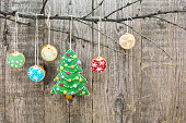 gingerbread christmas tree with cookies hanging over aged wooden background
