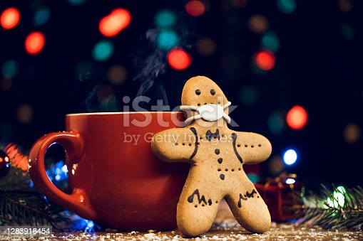 Gingerbread cookie wearing face mask and red cup on Christmas background