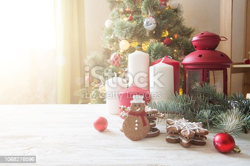 istock Gingerbread cookies and candles with christmas decoration on white wooden table against christmas tree 1068276596