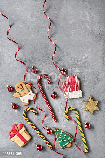 istock Gingerbread cookies, candies cane , tinsel and Christmas balls on a gray textured background. Top view, flat lay. 1173611386