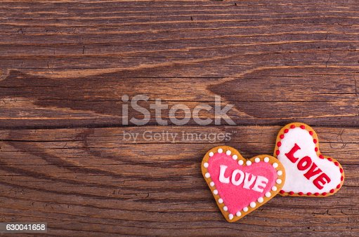 istock Gingerbread cookies with icing heart shaped on wooden table. 630041658